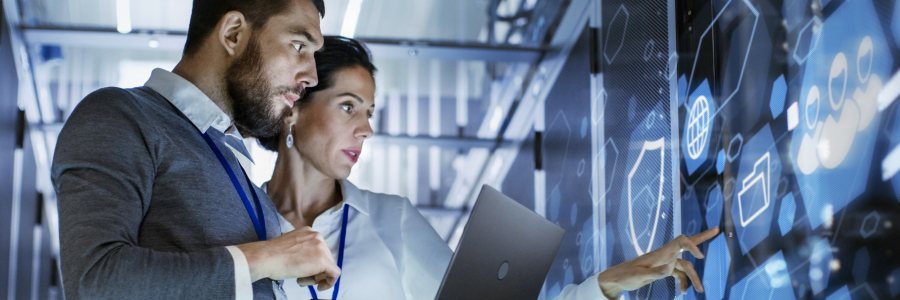 Male IT Specialist Holds Laptop and Discusses Work with Female Server Technician. They're Standing in Data Center, Rack Server Cabinet with Cloud Server Icon and Visualization.