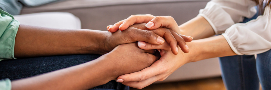 Close-up of psychiatrist hands together holding palm of her patient. Hands of woman reassuring her colleague. Diverse women. African american family couple holding hands